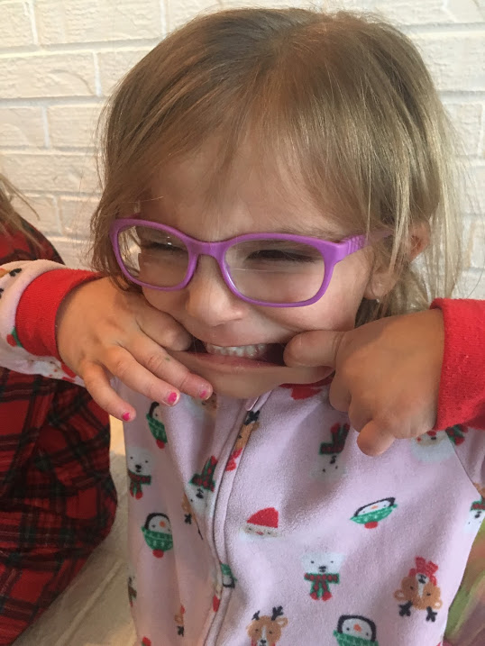 "Elle, a fleece-pajama clad 3-year-old with purple bifocal glasses is using her hands to stretch her mouth into a ""silly face."""