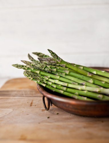 A bunch of green asparagus spears in a brown wooden bowl on a butcher block table.